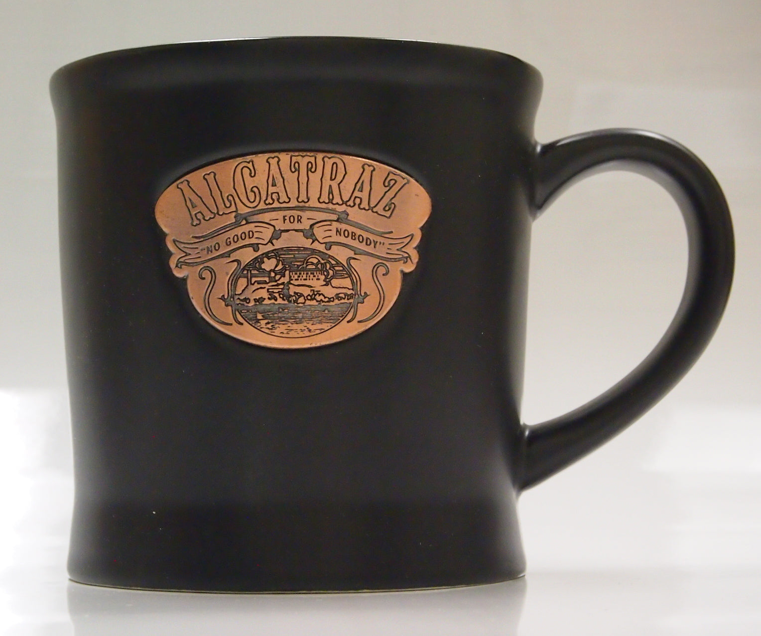 Large Black Ceramic Coffee Mug, with a Alcatraz badge on its side.