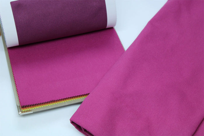 swatch book with pink fabric and finish of bottom of pink curtains