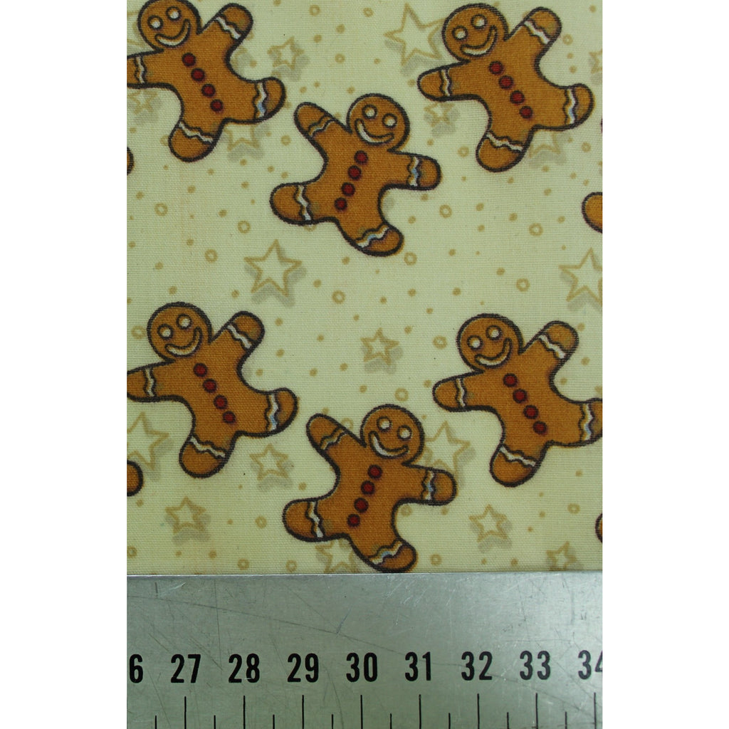 smiling gingerbread men in tan colour on a pale yellow background with stars and dots polycotton fabric