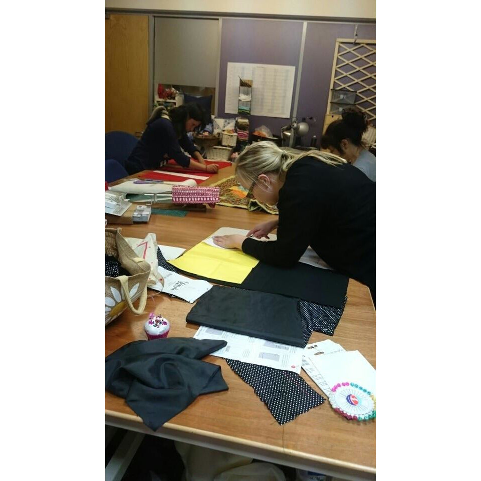 students cutting out on large cutting table in class room. Sewing course madonsewing