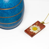 Copper coloured resin necklace with white flower and gold-leaf decoration