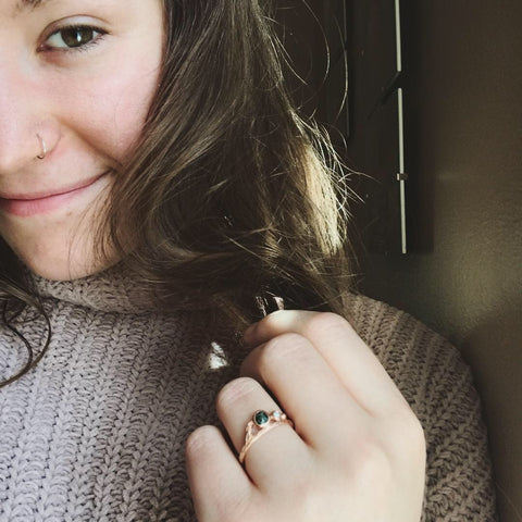 Shop assistant wearing a rose gold and greenstone ring by beth millner jewelry