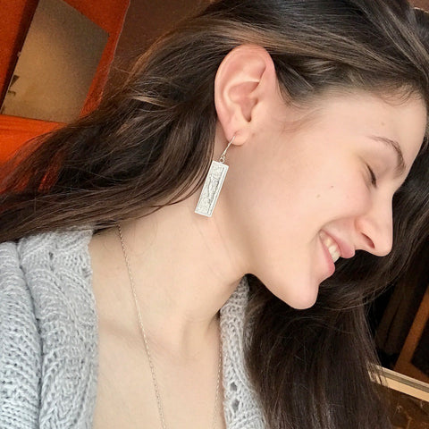 Shop assistant wearing recycled sterling silver woodpecker earrings by beth millner jewelry