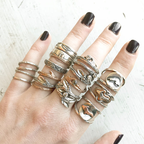Hand featuring a variety of rings in sterling silver and gold by Beth Millner Jewelry