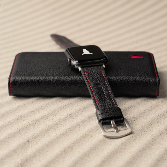 Black Leather Strap (with Red Stitching) for Apple Watch lying on a phone case