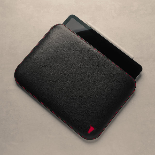 Demonstrating an iPad sliding into a Black with Red Detail Leather Sleeve