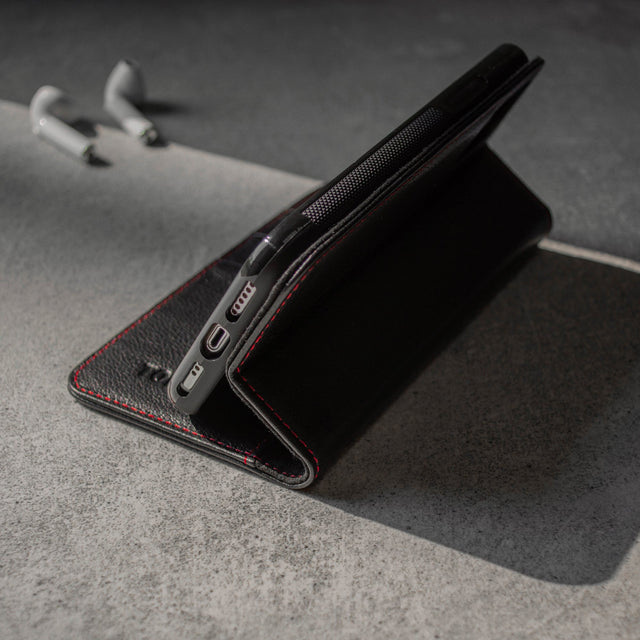 Demonstrating the integrated stand feature of the Black Leather (with Red Stitching) Stand Case for iPhone 11 Pro