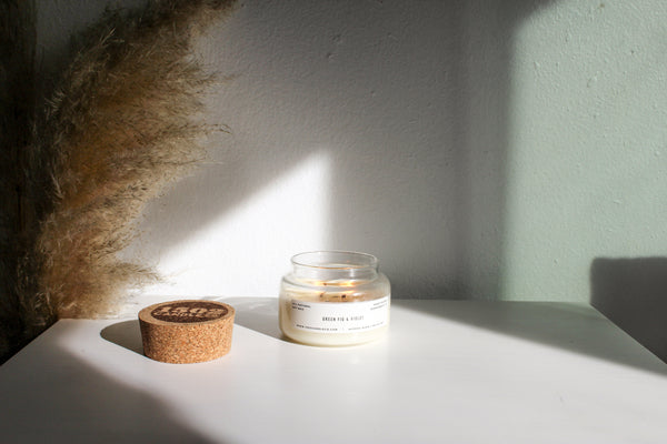 A 1502 Apothecary jar candle sits on a white table with the sun shining on the and a piece of pampus grass in the background.