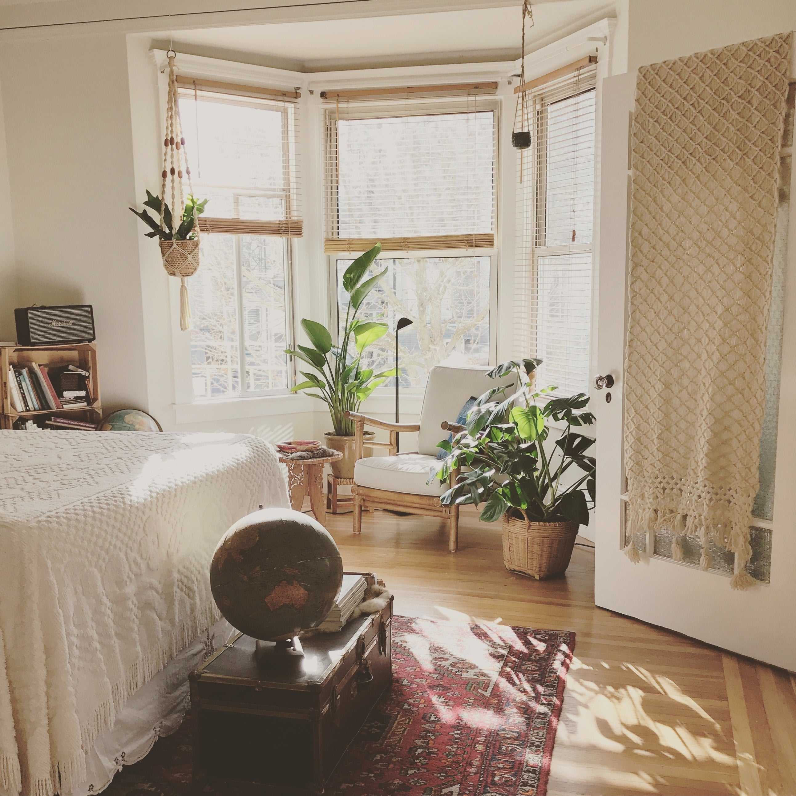 A bedroom with a sunny window and house plants though out it.
