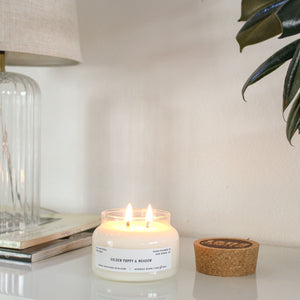 A Golden Poppy and Meadow candle sits lit with a lamp to the left of it and green leaves in the right corner.