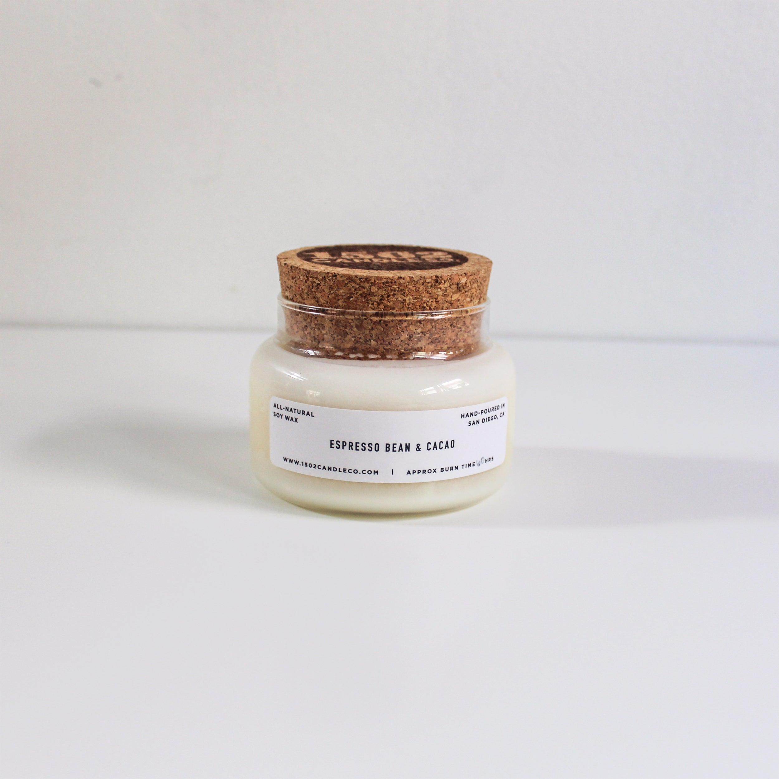 An epresson bean and cacao candle with cork lid sit on a white background.