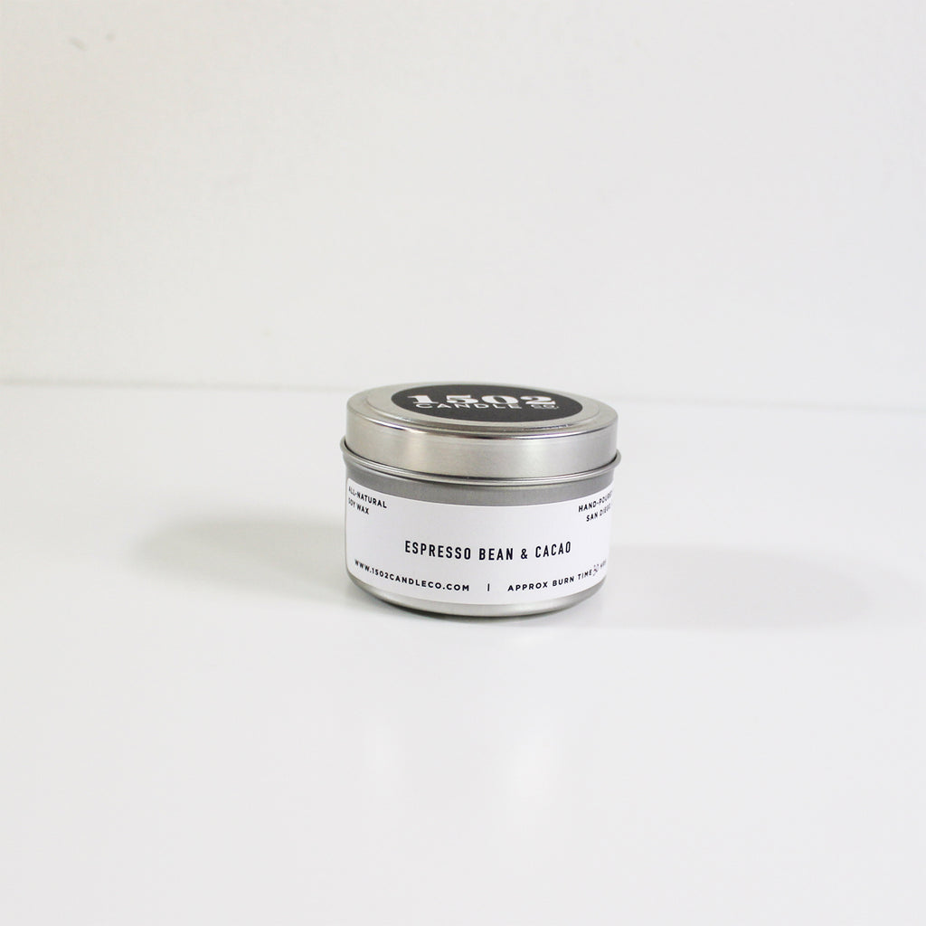 An espresso bean & cacao travel tin candle sits on a white background with lid on.