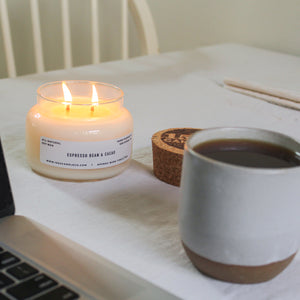 A two wicked espresso bean and cacao candle sits on a table with white table cloth with a mug of coffee and laptop.