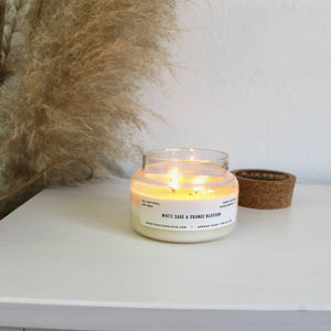 A lit white sage and orange blossom soy wax candle with cork topper off to the side and pompass grass.