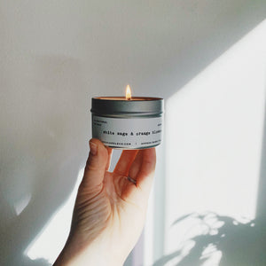A light skin toned hand holds a lit white sage and orange blossom candle up against a wall with shadows of plants on it.