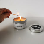 A light skin colored hand hold a lit match above a lit Lavender Blooms and Oud Travel Travel Tin Candle on a white table and background.