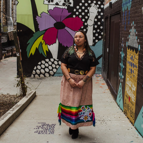 Ojibwe artist Caitlin Newago standing in Black Cat Alley in Milwaukee, Wisconsin. Brightly colored murals are behind her, she wears a black short sleeve blouse and a birchbark patterned ribbon skirt with bright rainbow colored ribbon and Ojibwe floral applique work.
