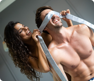 couple doing BDSM - woman putting blue blindfold on man - to show that cooling lube is a great beginning to temperature play for couples