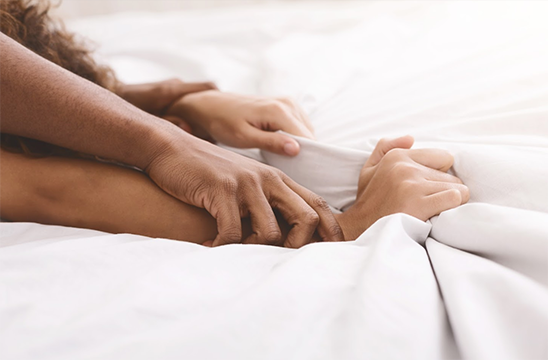 up-close photo of pair of hands on bed sheets as an interracial couple shares an intimate moment while using Lubilicious' Feel the Heat warming lube