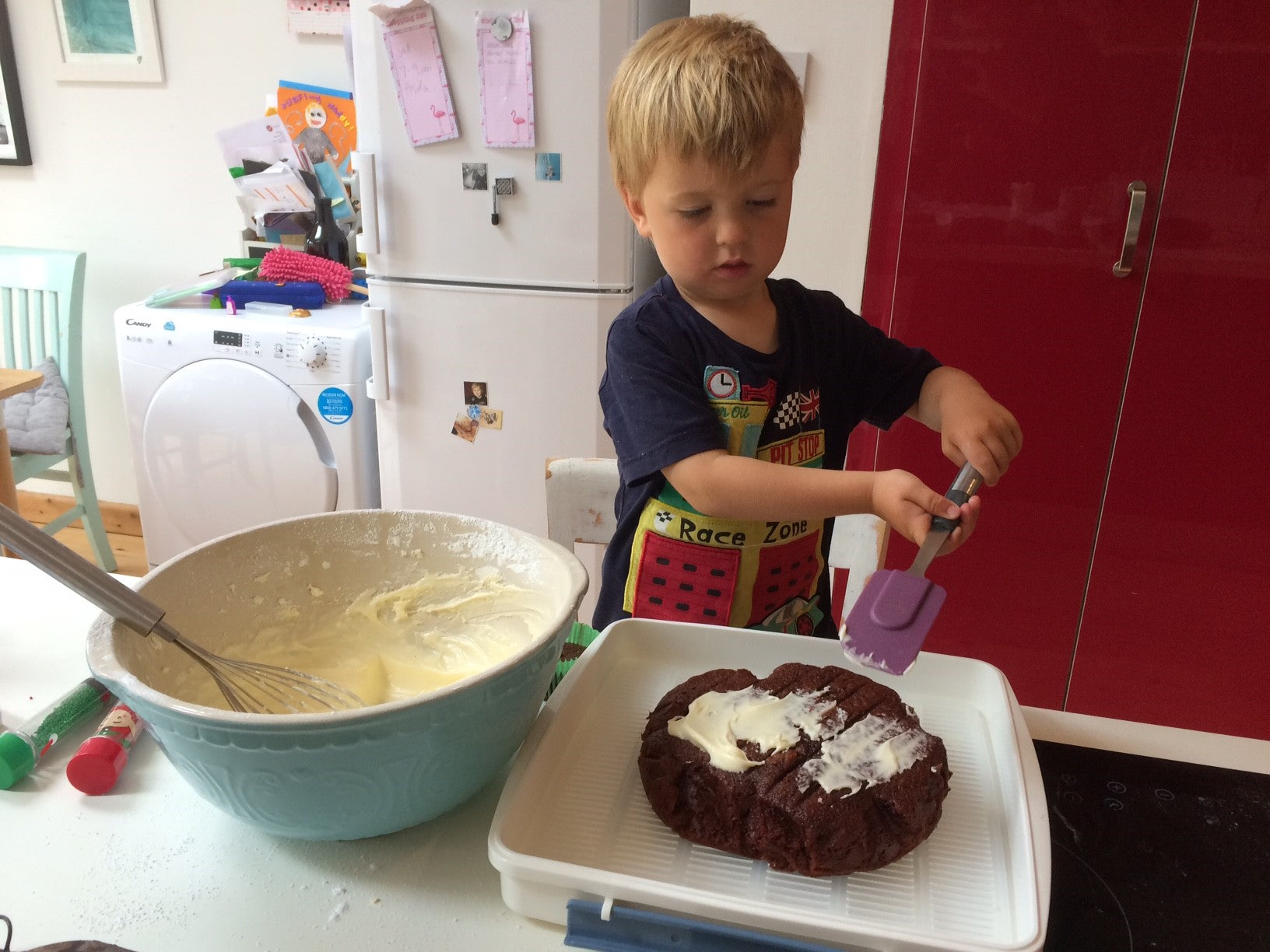Aaron's eldest helping to ice the birthday cake   Little Lockdown Lessons: Food for Thought