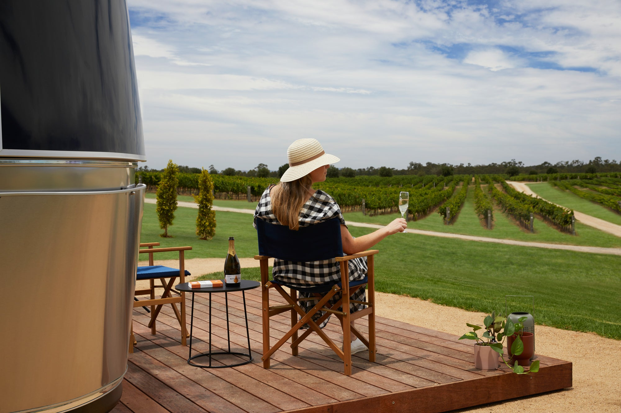 A womans sips champagne relaxing on a deck of an Airstream caravan on a vineyard