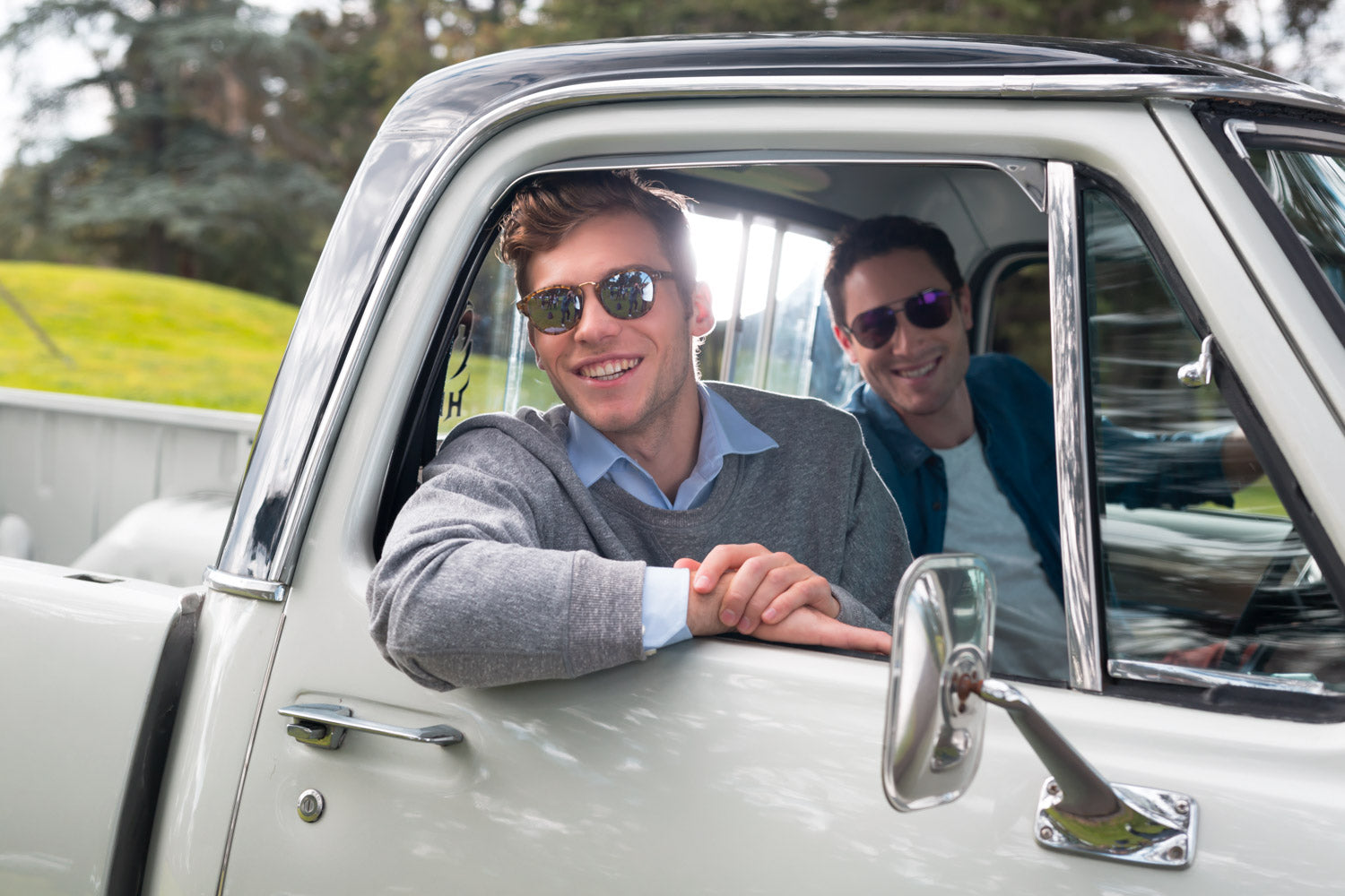 2 make models in a sitting in a vintage truck wearing sunglasses & smiling. They are parked in a park