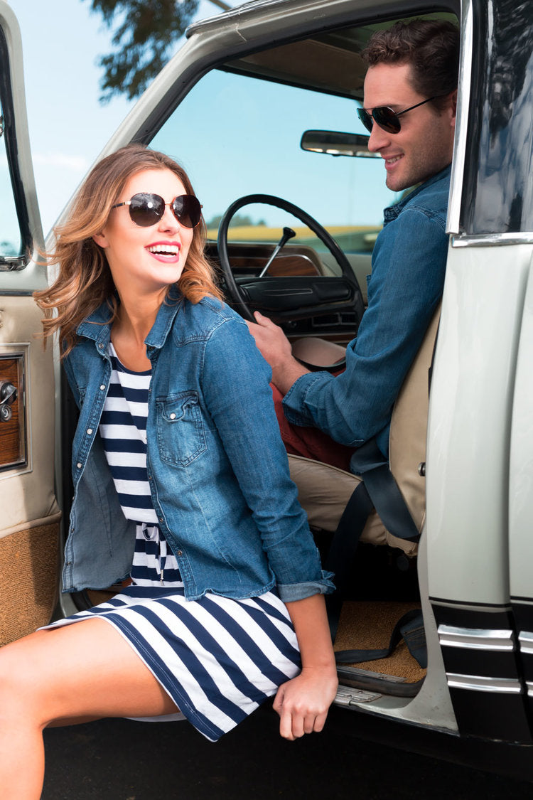 A young model sits in the doorway of an old vintage truck laughing with her boyfriend who is in the track