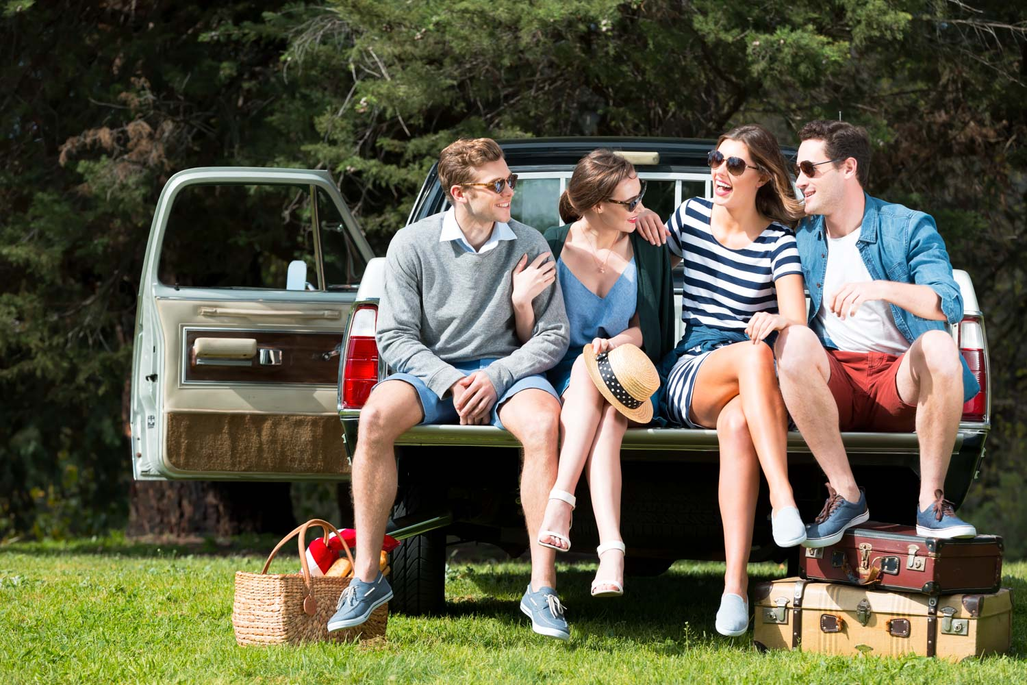 Two young couples sit on the back of a vintage truck with picnic blankets & they are smiling. The truck is in a park.