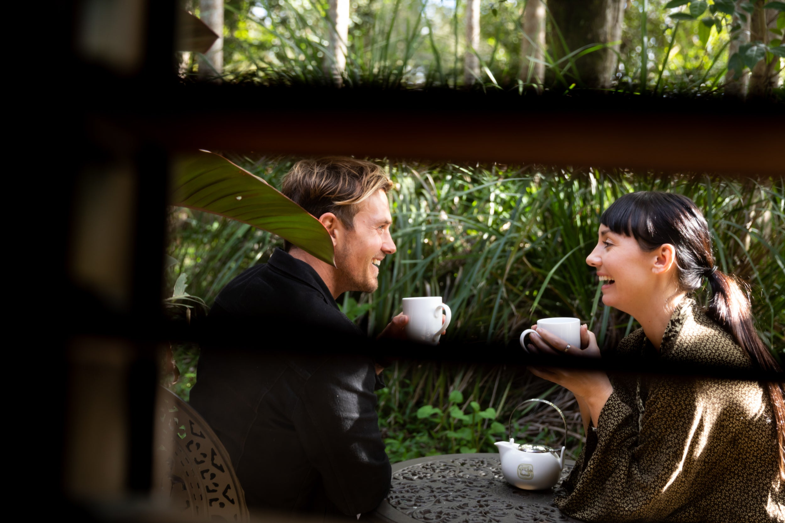 A young couple sit ourdoors & hace coffee & smile at each other. The photo is taken through a window lookling at them. They scenery is green & lush. lifestyle photography, fashion photography, A couple drink coffee together outside their room on their honeymoon
