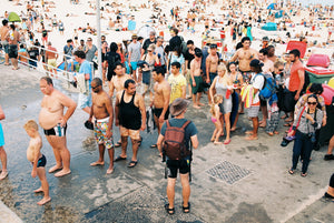 """A photo of New Years day at Bondi Beach, Thousands of people on the beach & in the water. People cue to have a shower in a long line. People are wearing bathers, it's a hot day in Sydney Australia."