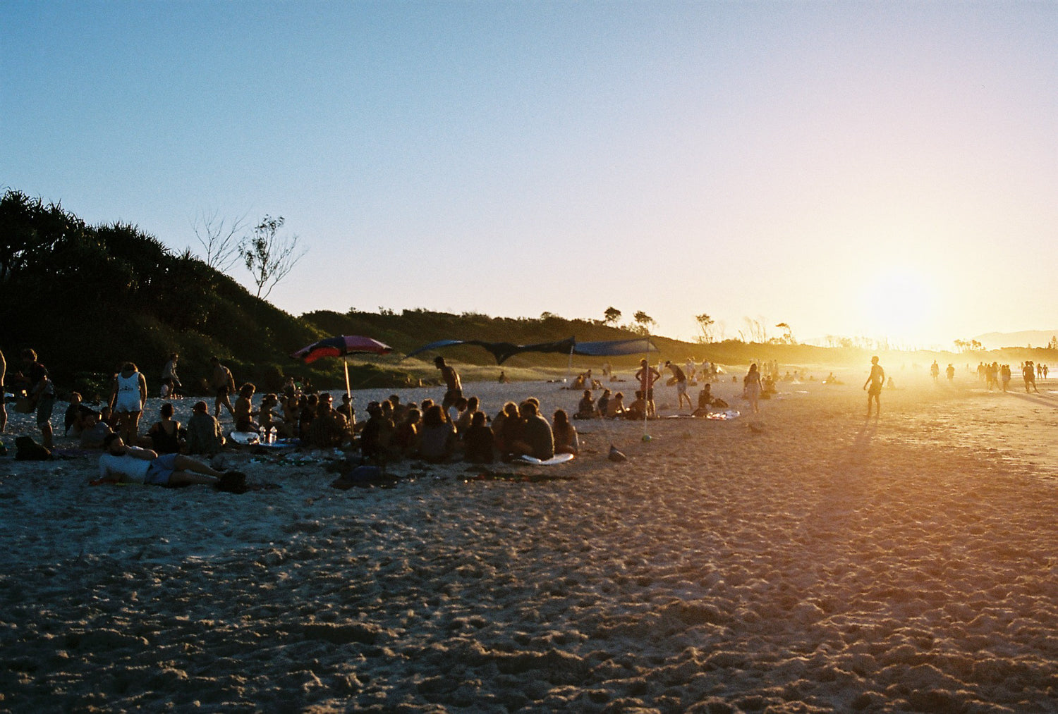 People sit in groups on the beach at sunset in Byron bay. The sun is low & the beach & blue water looks warm.  People are walking in the distance.