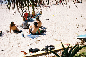 A group of hip young mens relax on the beach at Wategos beach in Byron bay.