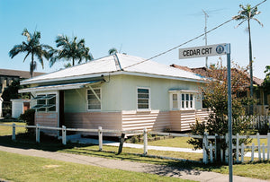 A 1950's beach house painted pink & white with a tin roof, retro style windows located on the Gold Coast of Queensland Australia. The sky is blue & there are tall palm trees. Artwork Prints, wall art, GoldCoast Queensland, Australia, Photographic prints, Ocean, Beach, Framed artwork, Beach Posters, Australian Photography, Photography for sale, Film photography ,Vintage photo style Interior design, Film photography, Pictures, sun, surf , wall art, prints for sale, architecture,