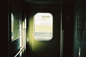 A photograph of the inside doorway in a fast moving train to Osaka Japan. The doorway is green.