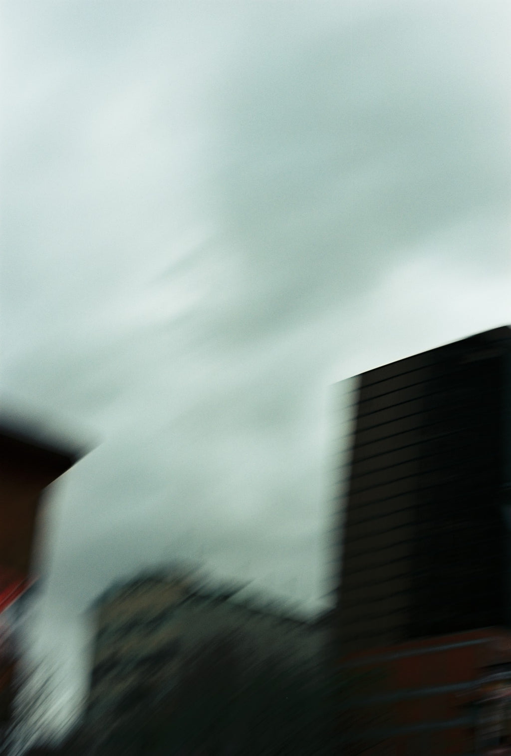 A photograph is a city building on a dark day with motion blur.
