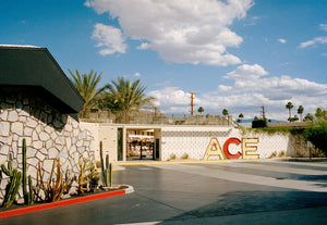 A photograph of the outside of the Ace Hotel in Palm Springs California. There is a large mid century sign that says ACE Blue skies & clouds with palm trees in the background. USA, Artwork, Prints, wall art, California, Photographic prints, Ocean Palm Springs, Framed artwork, Photography,  Film photography, Vintage photo style,  Interior design, beach, buy Art, photography art, buy art, ace hotel, Prints for sale, art prints, colour photography, sun, beach, sun baking, retro, interior design artwork,