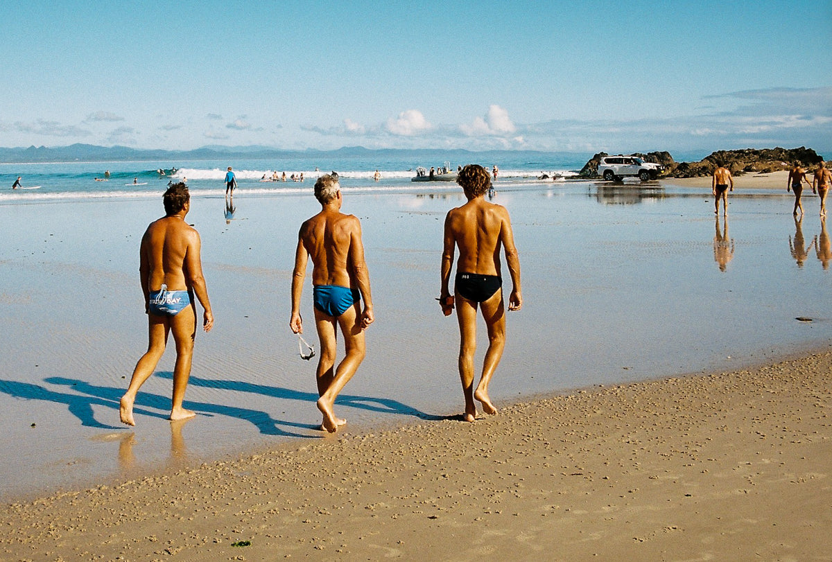 Three local men in speedos walk along Byron Bay's clarkes beach ready to go for a swim