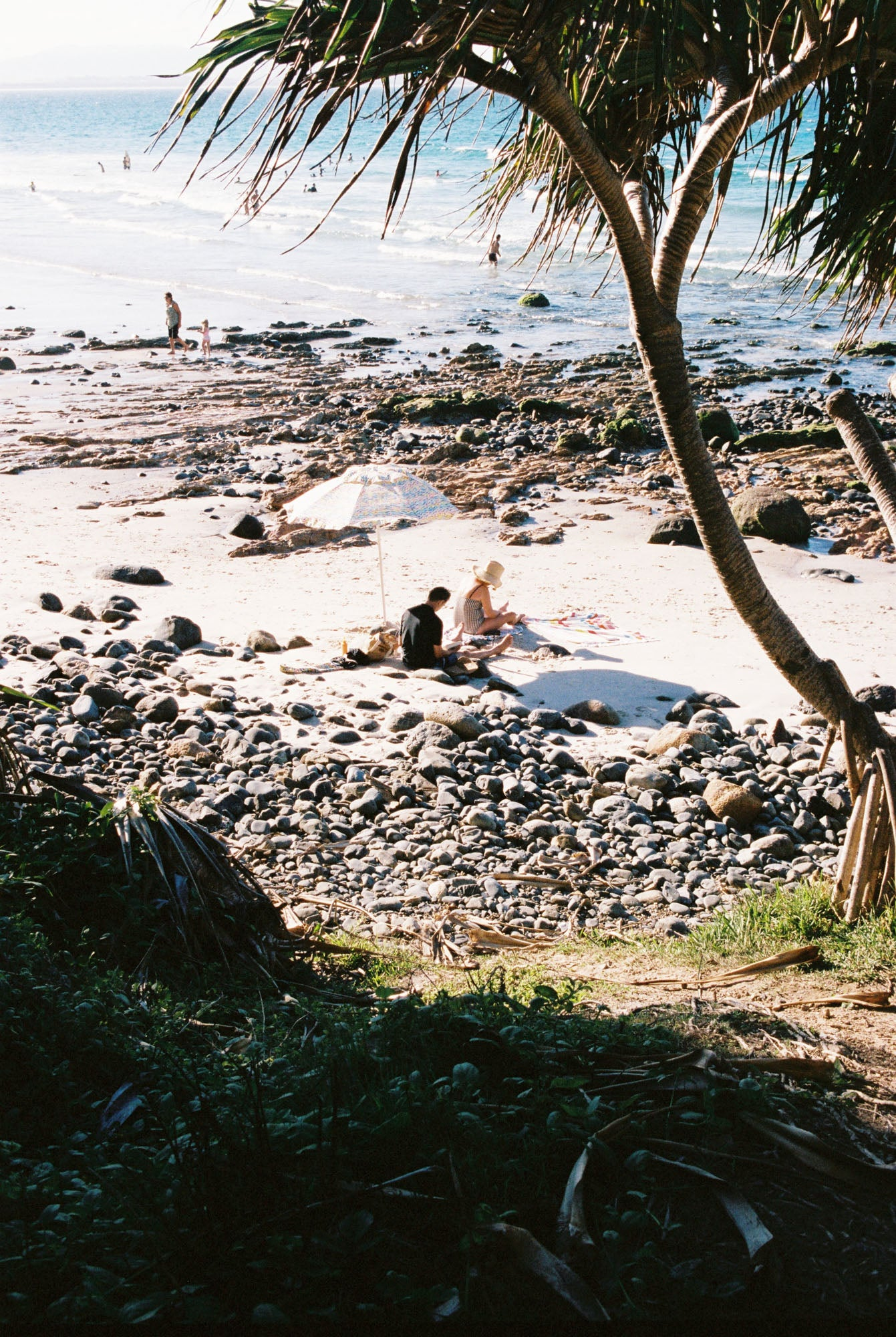 a couple read books on the beach under an umbrella in Byron bay. Palm trees & blue water