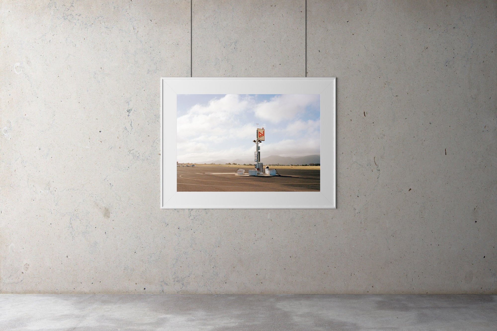 A photographic print gallery with an image on the wall. A photograph of an old airfield with a petrol filling station & old airplanes in the photo. Blue skies & clouds in the background. USA