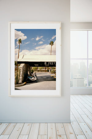 A photograph of a mid century motel in Palm Springs. There is an entrance with stone walls wth old scooters parked outside, there are palm trees & blue skies. USA, Artwork, Prints, wall art, California, Photographic prints, Ocean Palm Springs, Framed artwork, Photography,  Film photography, Vintage photo style,  Interior design, beach, buy Art, photography art, buy art, ace hotel, Prints for sale, art prints, colour photography, sun, beach, sun baking, mid century, swimming pool, interior design artwork,