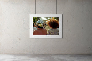 A colour photograph of two women sitting down at a music festival in the Australian countryside. The photo is taken from behind the women. One has a red afro hair style, the other wears a silver mirrorball helmet on her head. .Artwork Prints, wall art, Melbourne travel, Australia Photographic prints, Framed artwork, Australian Photography, Film photography, Vintage photo, style Interior design, Pictures, Abstract, film photography, photography for sale, music festival,