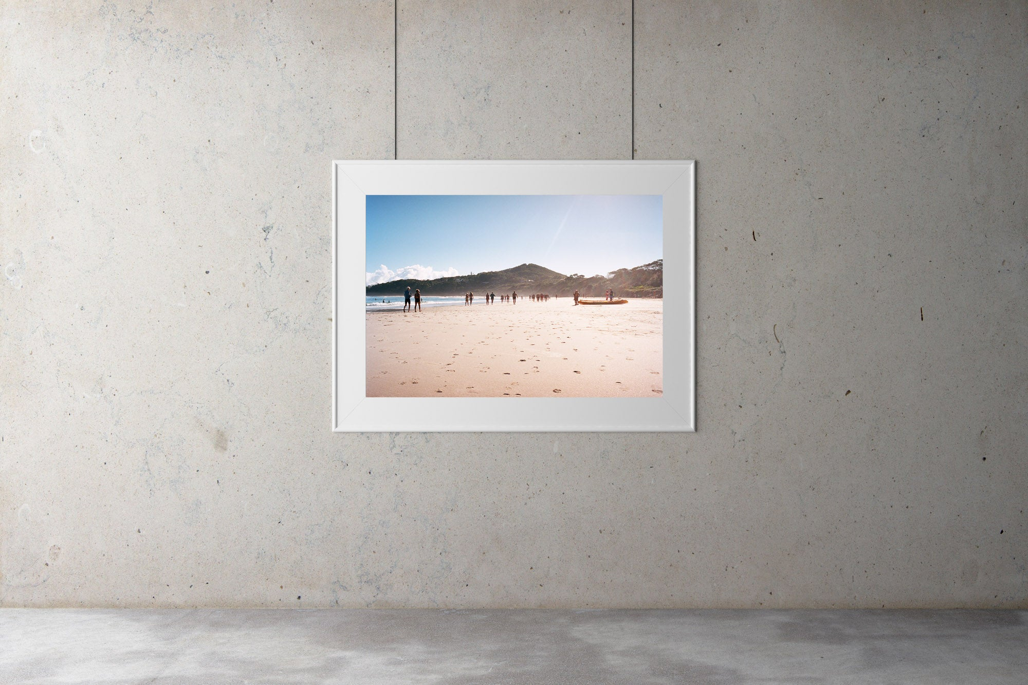 A photography galley with a print on the wall, Byron bay beach with people walking in the distance, blue calm water, blue sky. Two men on a kayak head to the water, Artwork Prints, wall art, Melbourne travel,  Photographic prints,  Framed artwork,  Australian  Photography, wall art, beach prints, coastal prints, ocean prints,  Film photography, Vintage photo, style  Interior design, Pictures Abstract film photography, photography art, Australia, sun, beach, Byron bay,