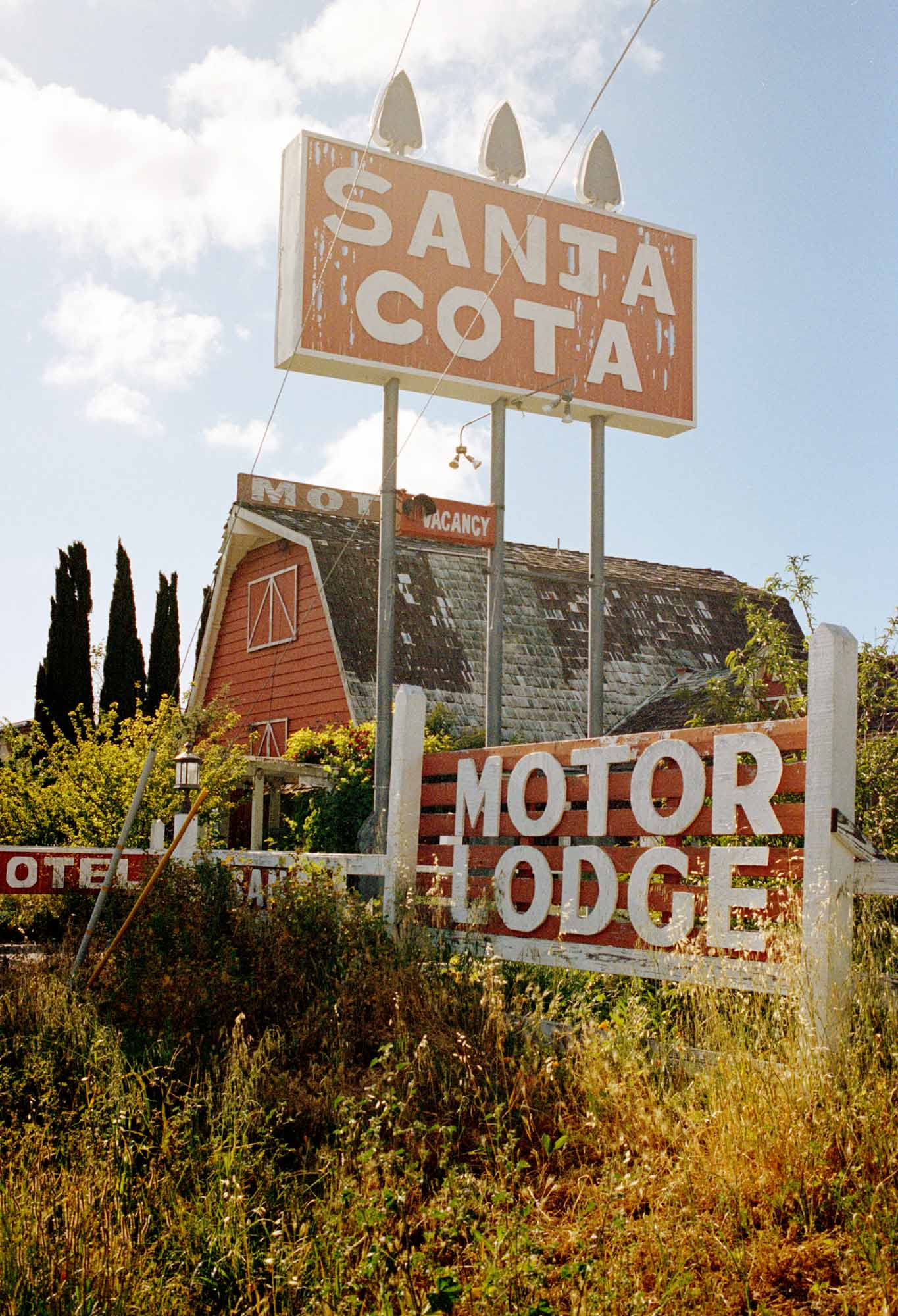 A photograph of an old 1950's American Motel. Large signs out the front & overgrown vegetation. The Motel is Barn style.