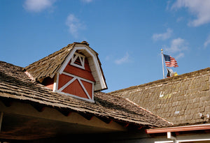 A vintage motel with shingle roof tiles & farmhouse barn roof features. There is an American flag on the roof. There are blue skies. Film photography, Vintage photo style,  Interior design, buy art, photography art, buy art, Prints for sale, art prints, colour photography, vintage photo style, American flag, California, pioneer,