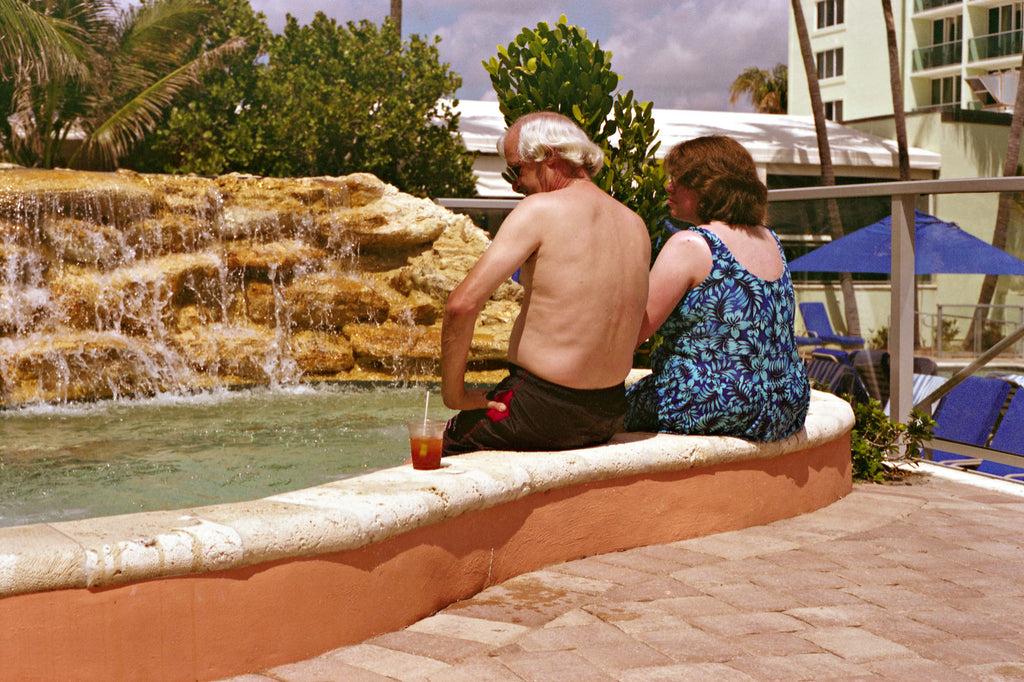 A couple sit next to a rock pool in a Miami hotel drinking cocktails wearing 1980's swim suits.