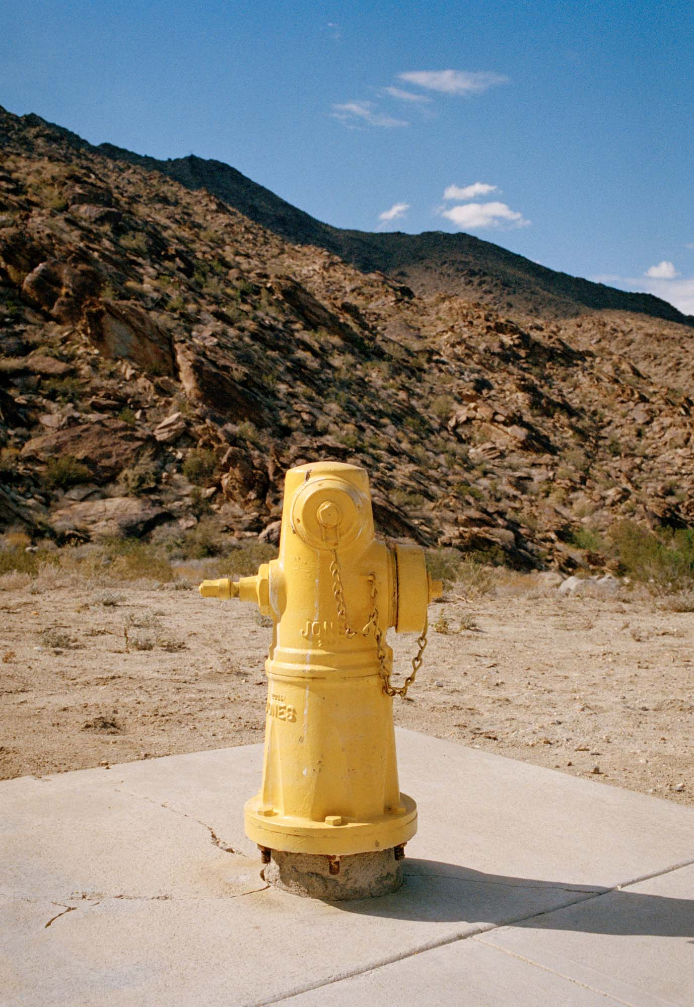 A photography of a yellow fire hydrant sitting in the desert of Palm Springs California.
