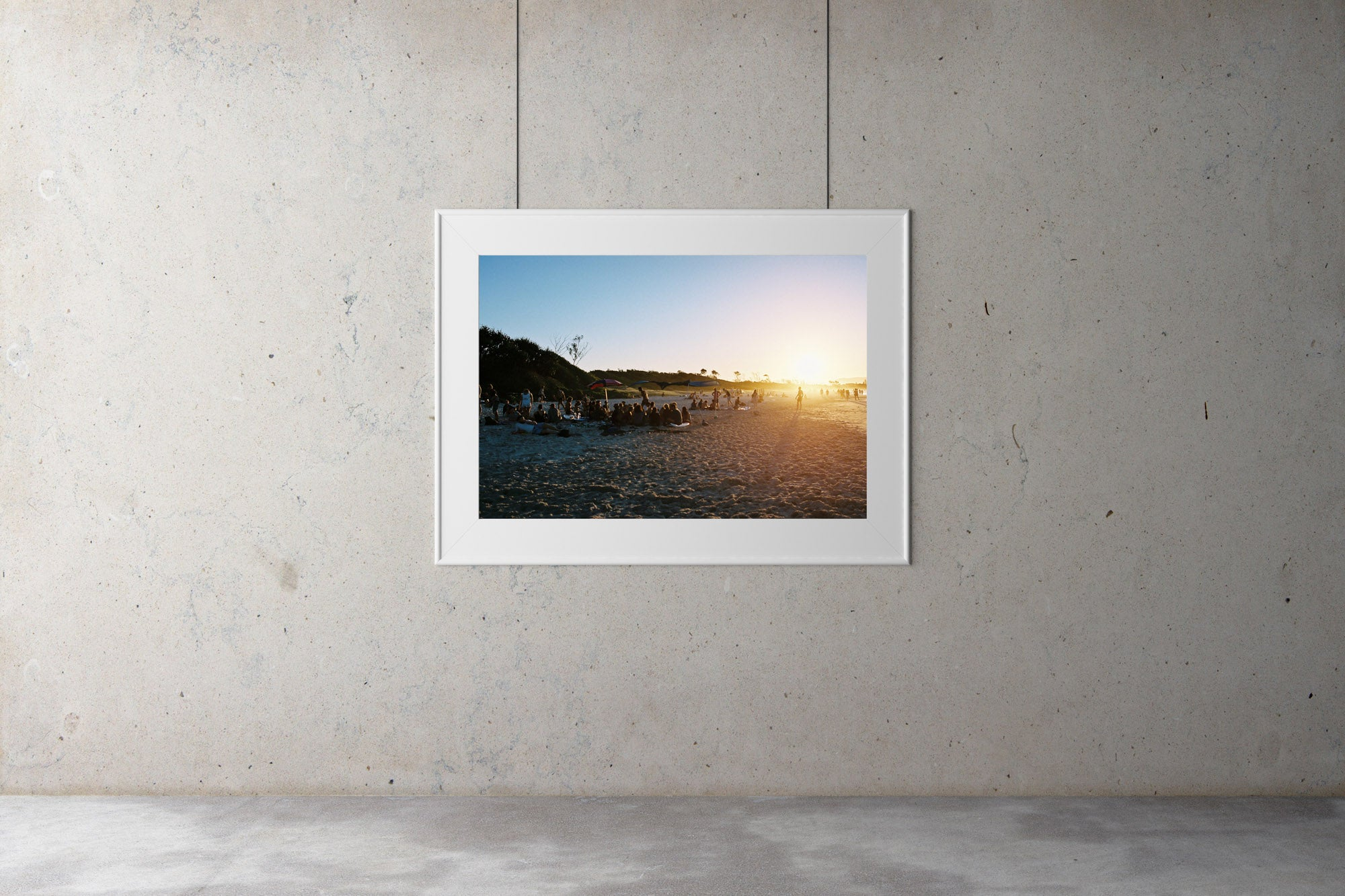 People sit in groups on the beach at sunset in Byron bay. The sun is low & the beach & blue water looks warm.  People are walking in the distance, blue calm water, blue sky.  Artwork Prints, wallart,  Photographic prints,  Framed artwork,  Australian  Photography, wall art, beach prints, coastal prints, ocean prints,  Film photography, Vintage photo, style  Interior design, Pictures Abstract film photography, photography art, Australia, sun, beach,