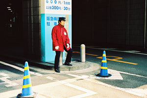 A parking attendant sitting outside a Japanese carpark entrance. He wears a red uniform with a black cap in Toykp Japan.