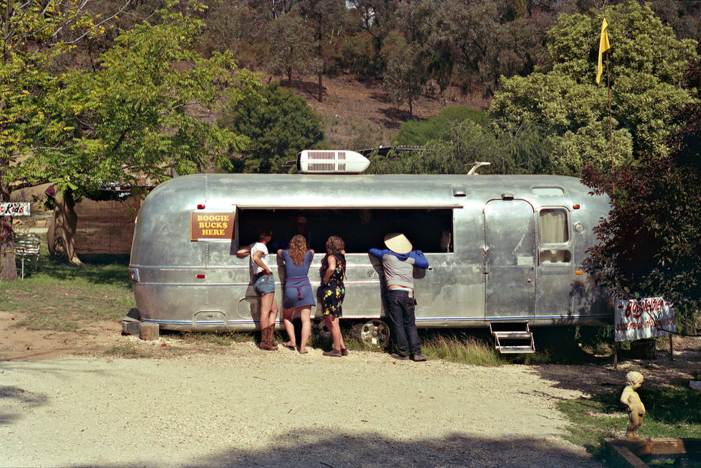A photograph of a vintage Winnebago caravan selling drinks at a music festival in the Australian countryside. There are 3 people standing outside ordering drinks from the vendor in the van. Artwork Prints wall art,  Melbourne travel ,Australia Photographic prints, music festival, Framed artwork, Australian,  Photography, Photography for sale, Film photography, Vintage photo style,  Interior design, Film photography, Pictures,  art, film photography,
