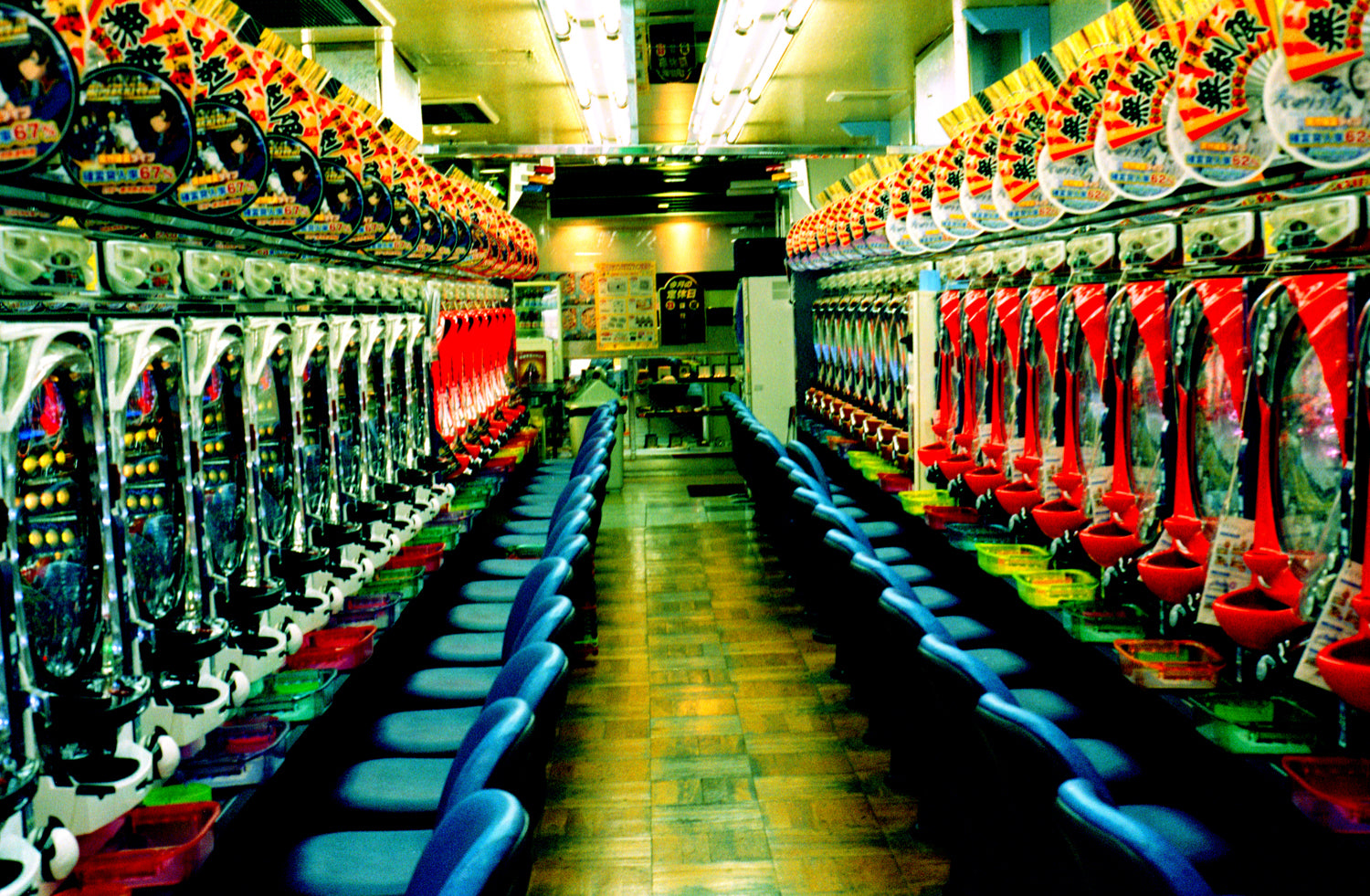 A pinball arcade in Tokyo Japan. Red, green & yellow neon lights shine.